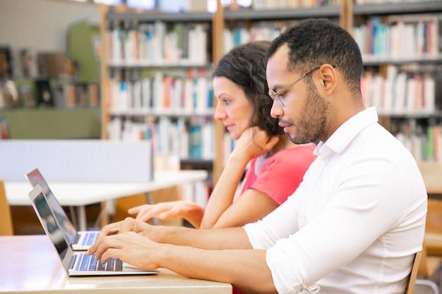 Estudiantes universitarios que trabajan en la clase de informática de la biblioteca