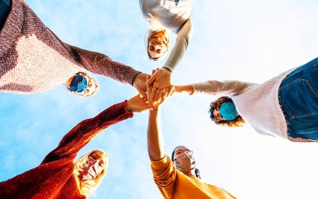 Estudiantes universitarios trabajo en equipo apilando las manos