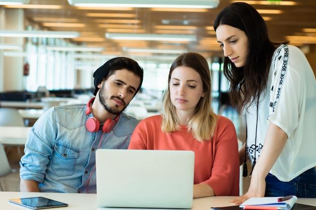 Estudiantes universitarios utilizando la computadora portátil en la biblioteca universitaria.