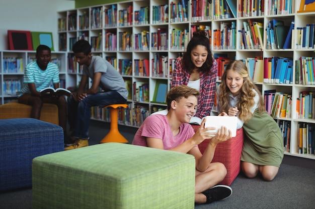 Estudiantes usando tableta digital en biblioteca