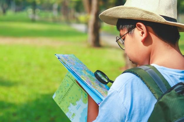 Estudiantes varones asiáticos llevando una mochila de viaje, con un sombrero, sosteniendo un mapa para viajar para aprender