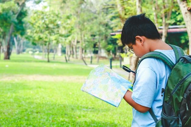 Estudiantes varones asiáticos llevando una mochila de viaje, sosteniendo un mapa para viajar para aprender