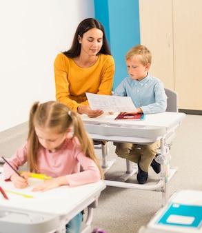 Estudiantes de vista frontal sentados en su escritorio en clase