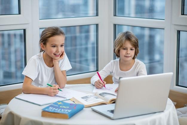 Estudiar desde casa. hermanos estudiando en casa y haciendo lecciones juntos.