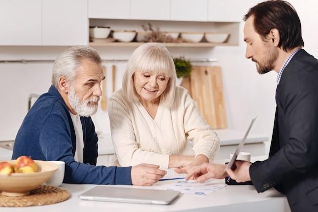 Estudiar detalles. feliz pareja de ancianos concentrados sentados en casa y discutiendo el contrato con el agente de bienes raíces mientras intercambian opiniones