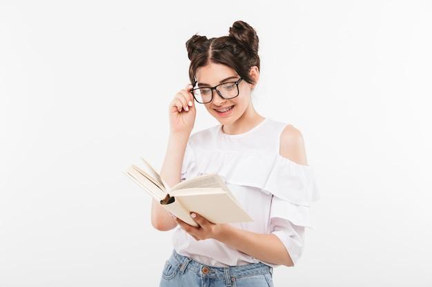 Estudiar estudiante o niña de la escuela con peinado de bollos dobles y aparatos dentales libro de lectura con interés, aislado en blanco