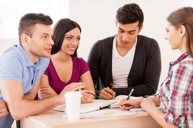 Estudiar juntos es divertido. cuatro estudiantes alegres que estudian juntos mientras están sentados en el escritorio