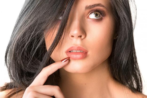 Estudio ascendente cercano pensativo hermoso de la cara morena de la mujer en blanco.