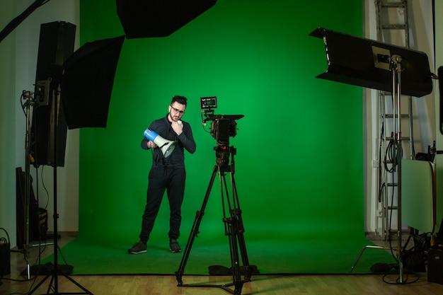 Estudio con cámara y lámparas y persona con altavoz.