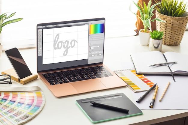 Estudio de diseño gráfico con diseño de logotipo en la pantalla del portátil.