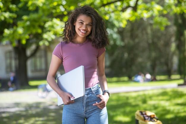 Estudio a distancia. una chica bonita de piel oscura estudiando en el parque.