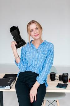 Estudio de fotografía y mujer sosteniendo una cámara