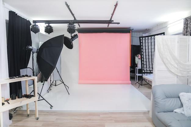 Estudio fotográfico vacío con equipo de iluminación profesional.