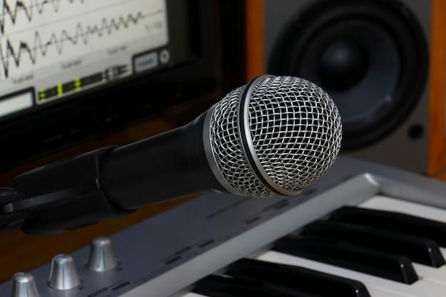 Estudio de grabación casero. pantalla teclado, parlantes y micrófono.