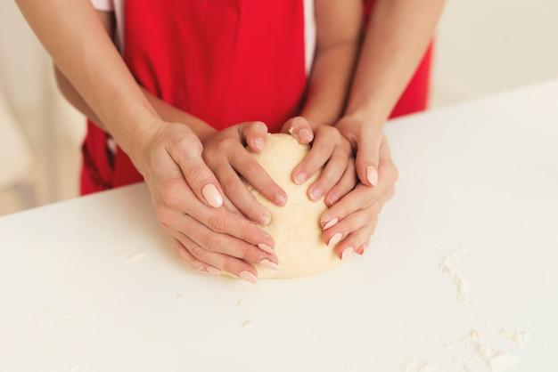 Estudio de mamá y jovencita hornear un pastel juntos.