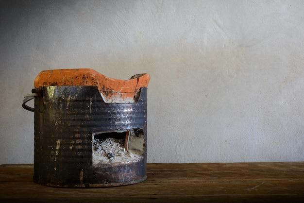 Estufa de carbón sobre suelo de madera.