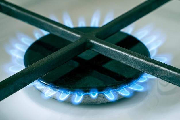 Estufa de gas, primer plano de una estufa con luz azul de gas