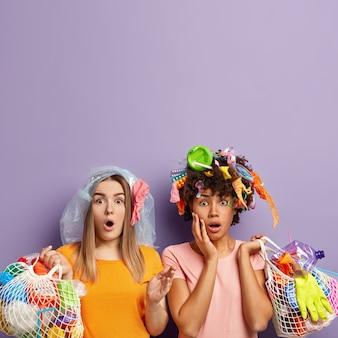 Estupefactas dos activistas miran fijamente con expresión omg, sorprendidas al recoger mucha basura, sujetan bolsas de red con desechos plásticos, vestidas con ropa informal, recogen basura para reciclar, espacio libre arriba