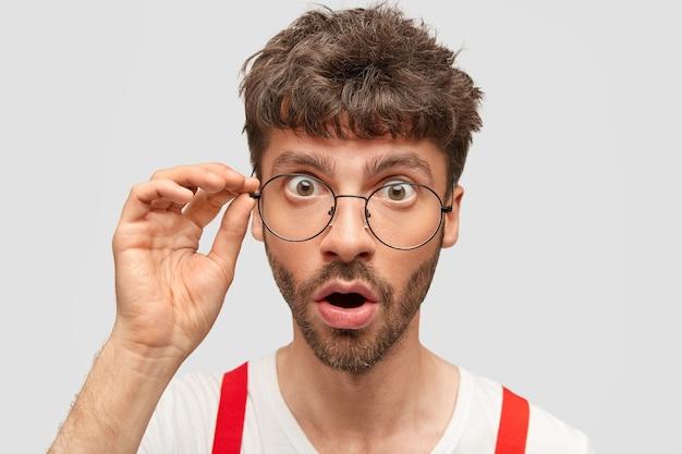 Estupefacto joven apuesto con apariencia europea, se da cuenta de su terrible error, toca el borde de las gafas