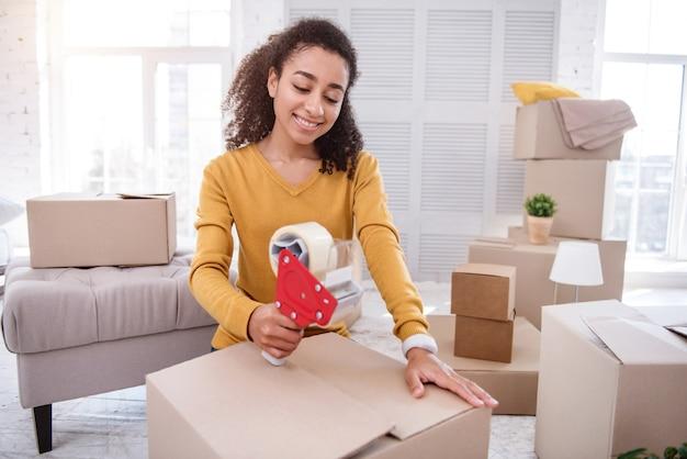 Etapa final. encantadora chica de pelo rizado cerrando una caja de forma segura con cinta adhesiva mientras se prepara para salir del piso