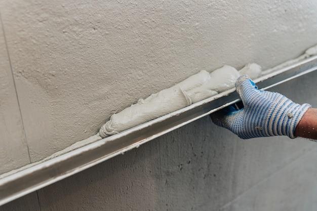 La etapa final de enlucido de las paredes. un trabajador nivela el yeso con un nivelador.
