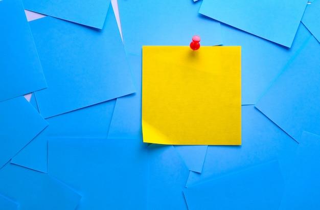 Etiqueta adhesiva amarilla para el recordatorio de información. espacio para texto. junto a él hay pegatinas azules vacías.