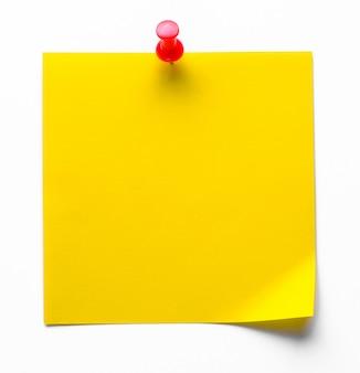Etiqueta adhesiva amarilla sobre un fondo blanco para recordar información, adjunta con un clip. espacio para texto.