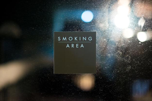 Etiqueta adhesiva de mensaje de área de fumar en el fondo de la puerta de gafas