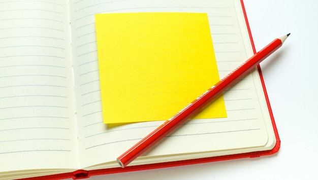 Etiqueta amarilla para recordar información en una página en blanco del bloc de notas abierto.
