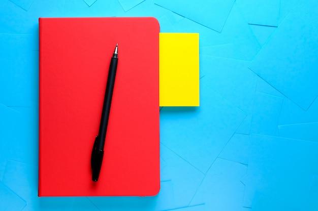 Etiqueta amarilla para un recordatorio de información que se adjunta al cuaderno rojo. hay una pluma al lado. el concepto de nuevas ideas, innovaciones, soluciones a problemas.