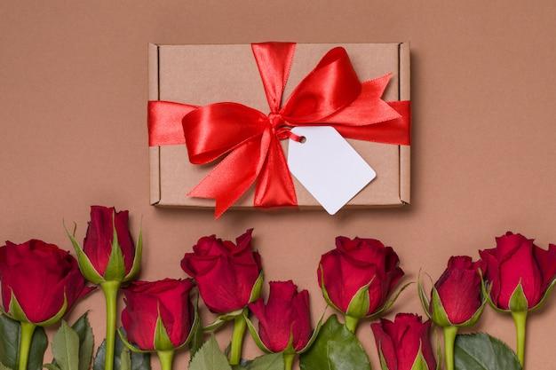 Etiqueta del arco de la cinta del regalo del día de tarjetas del día de san valentín, rosas rojas del fondo desnudo inconsútil
