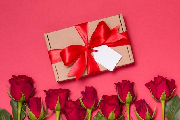 Etiqueta del arco de la cinta del regalo del día de tarjetas del día de san valentín, rosas rojas del fondo rojo inconsútil