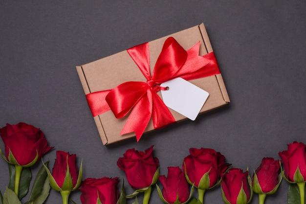 Etiqueta del arco de la cinta del regalo del día de tarjetas del día de san valentín, rosas rojas inconsútiles del fondo negro