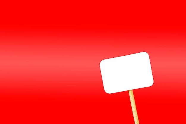 Etiqueta blanca sobre una pata de madera sobre un fondo rojo.