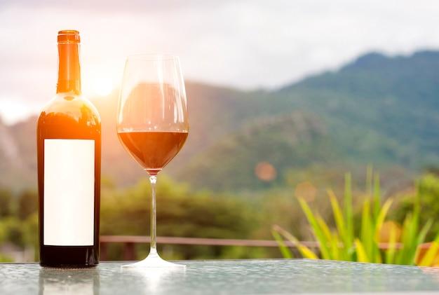 Etiqueta en blanco botella de vino tinto con una copa en la naturaleza