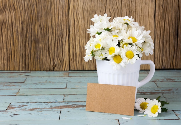 Etiqueta en blanco del papel marrón y margaritas frescas en la taza blanca en la tabla de madera