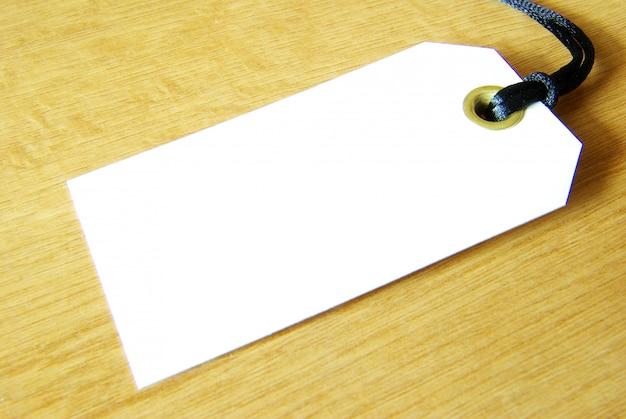 Etiqueta en blanco sobre mesa de madera