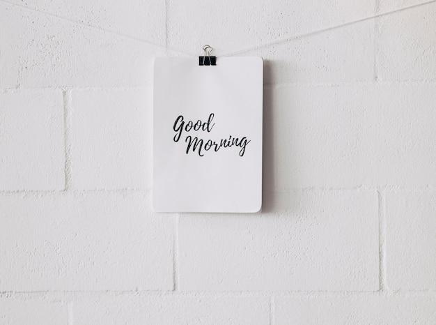Etiqueta de buenos días adjunta en una cuerda con un clip de bulldog contra una pared blanca