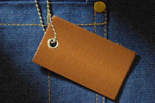 Etiqueta de cuero del precio del producto y cadena de bolas de acero inoxidable en ropa de mezclilla.