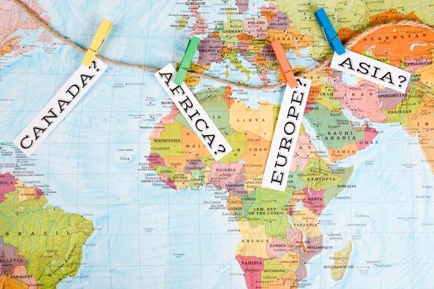 Etiqueta de diferentes continentes con pinza de ropa en el mapa mundial