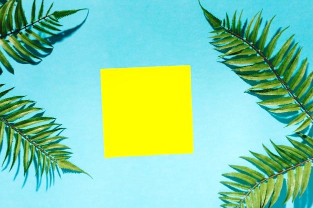 Etiqueta engomada enmarcada ramas de palma en superficie colorida
