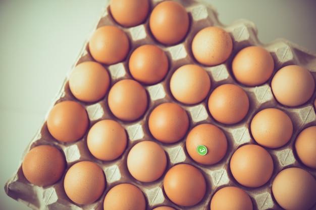 Etiqueta engomada número 3 en el huevo en la bandeja de papel, los huevos son escasos