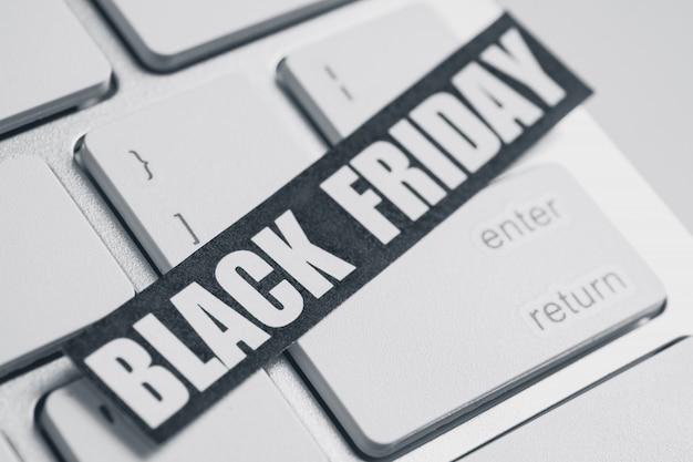 Etiqueta engomada del viernes negro en el teclado blanco.