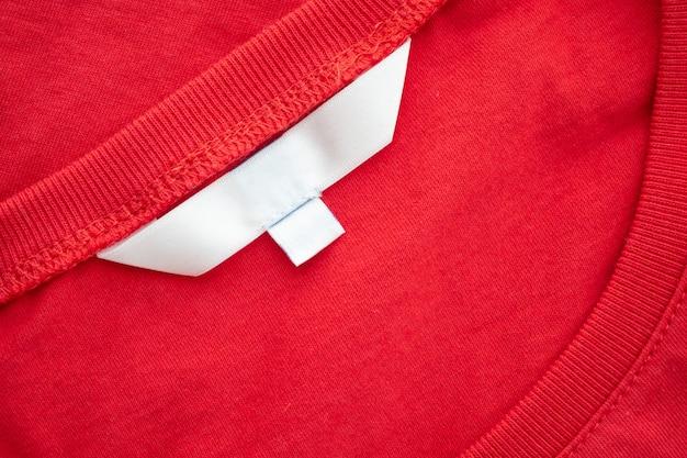 Etiqueta de etiqueta de ropa en blanco blanco sobre fondo de textura de tela de nueva camisa de algodón rojo