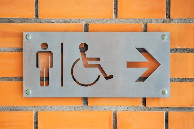 Etiqueta de inodoro masculino con discapacidad en la pared de ladrillo rojo