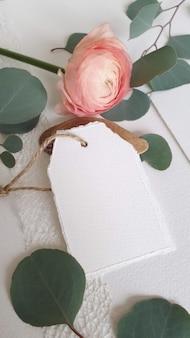 Etiqueta de invitación de saludo de boda blanco en blanco rama de hojas de eucalipto de plata, sobre fondo de mesa de papel con textura. plantilla moderna elegante vista superior plana