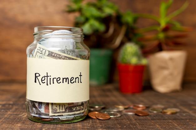 Etiqueta de jubilación en un frasco lleno de dinero y plantas en segundo plano.