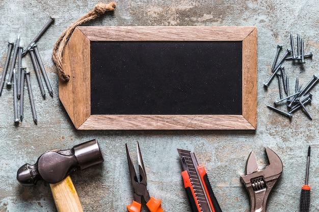 Etiqueta de madera en blanco con varias herramientas de trabajo en el escritorio de madera oxidado