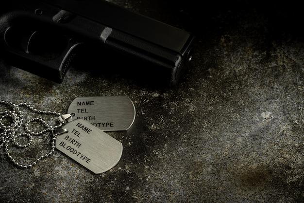 Etiqueta militar en blanco y una pistola en una placa de metal oxidada abandonada