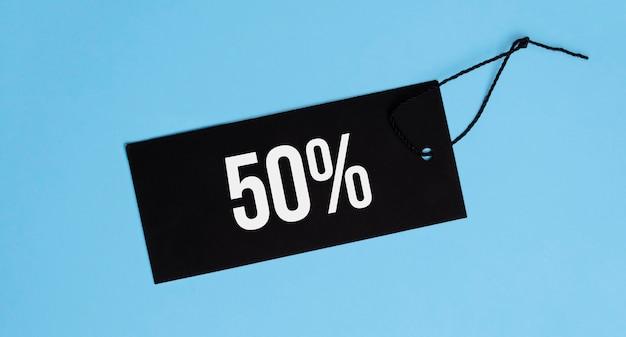 Etiqueta con palabras 50 por ciento de venta colgando sobre fondo azul. espacio para texto